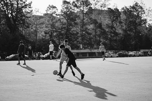 people grayscale photo of group of man playing soccer on field black-and-white