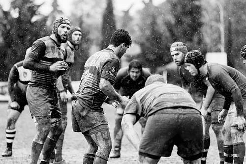 black-and-white grayscale photo of group of people on football field people