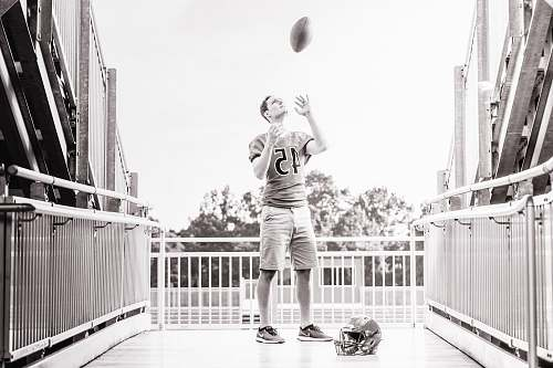person grayscale photo of man standing while tossing football outdoors people