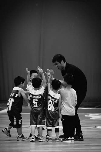 person grayscale photography of man standing beside kids wearing jersey shirts black-and-white