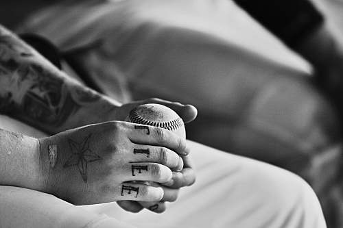 black-and-white grayscale photography of person holding baseball ball skin