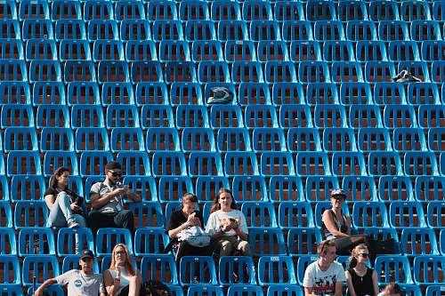 person group of people sitting on blue gang chair audience
