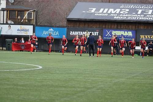 person group of women running on football field field