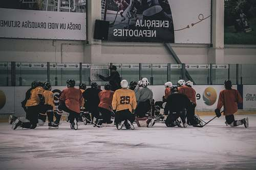 person hockey coach in front of hockey player people