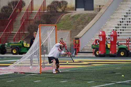 hockey lacrosse goalie defending goal on field at daytime people