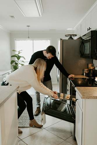 indoors man and woman by open range oven room