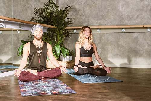 person man and woman doing yoga on top of yoga mats apparel