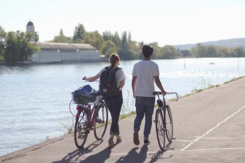 person man and women walking holding their bicycles beside body of water people
