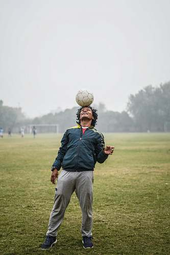 person man balancing a soccer ball on his head people