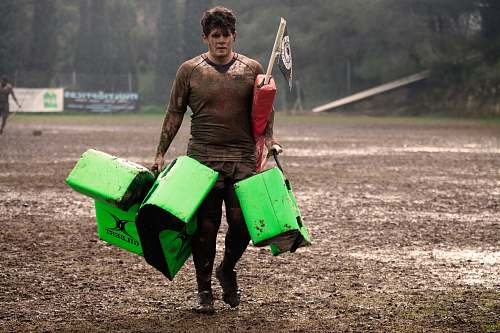 person man covered in mud carrying leather training pads people