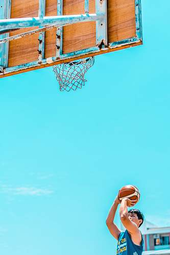 person man holding basketball in front of basketball system during daytime people