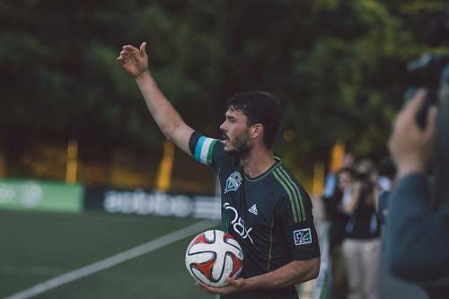person man in black and green Adidas jersey shirt holding soccer ball soccer