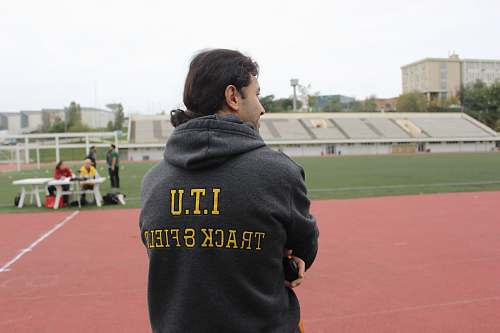 person man in black and yellow hoodie front of field people