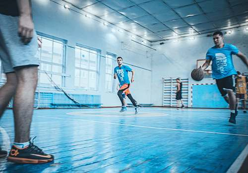 people man in blue t-shirt dribbling basketball person