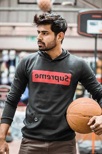 person man in gray Supreme hoodie holding basketball sports