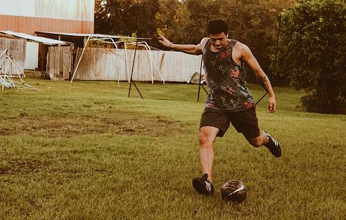 person man kicking football on grass field during daytime apparel