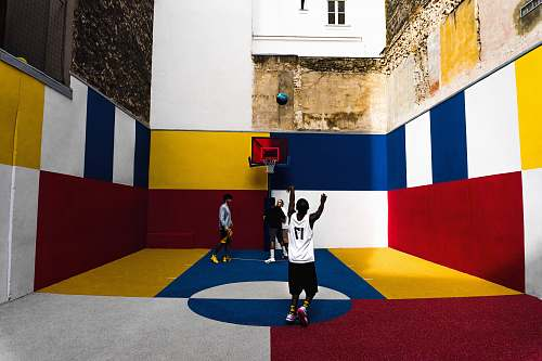 person man playing basketball inside multicolored court people