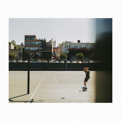 people man playing basketball on court during daytime person
