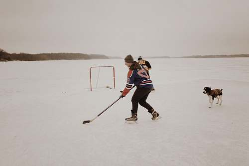 person man playing ice hockey dog