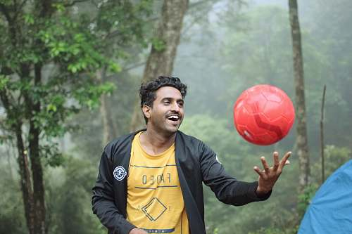 person man playing red soccer ball sphere