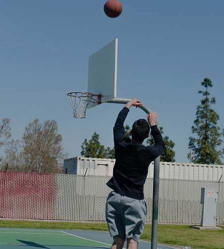 person man shooting ball on hoop during daytime people