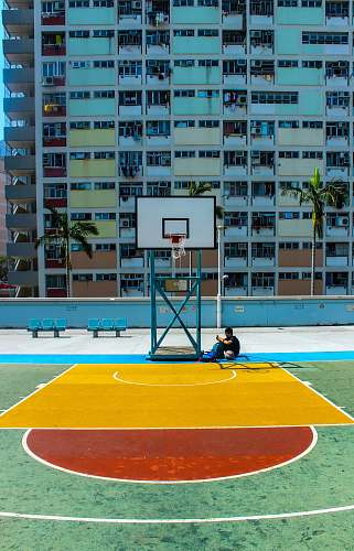 people man sitting below basketball hoop near the building during daytime person
