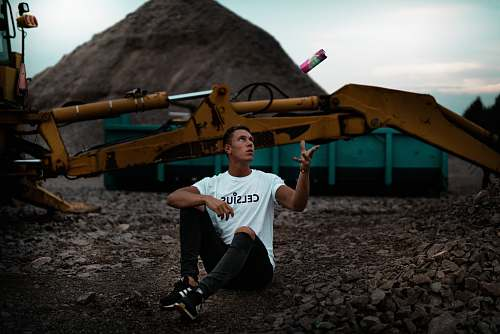 person man sitting on the ground near excavator people