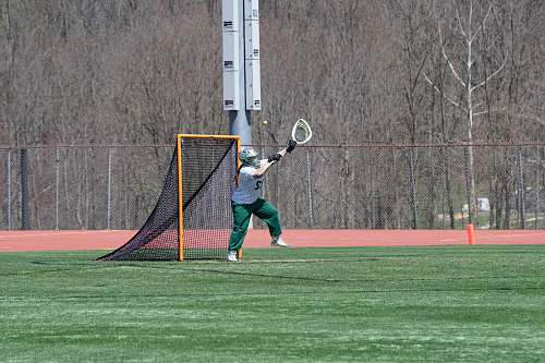 person man standing on field holding lacrosse stick racket