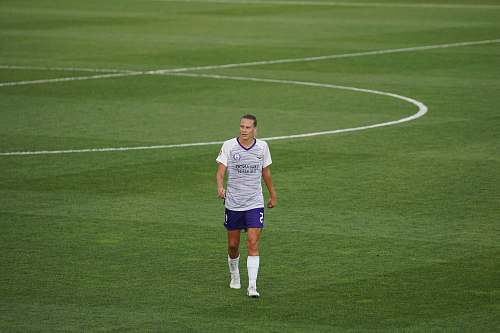 person man standing on soccer field during daytime people