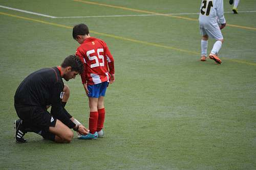 people man tying boy's shoes on field football