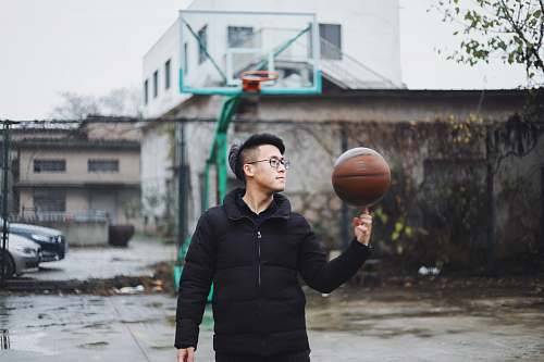 person man wearing black bubble zip jacket with basketball spinning on his right index finger people
