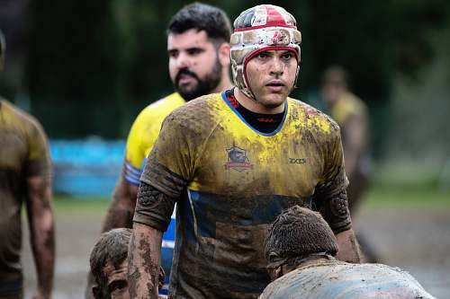 person man wearing yellow and blue shirt on mud field during daytime people