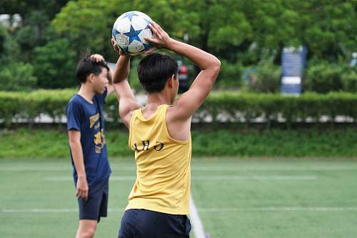 person man wearing yellow tank top holding soccer ball people