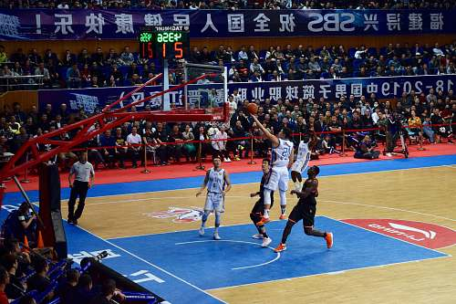 person men playing basketball game surrounded with people watching people