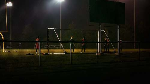 person men plays soccer during nighttime people