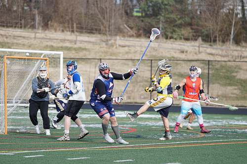 apparel people playing lacrosse during daytime person