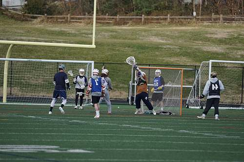 person people playing lacrosse game on field people