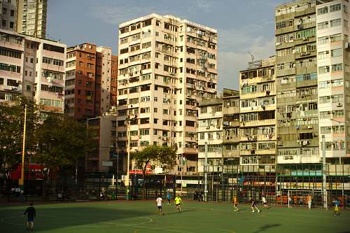 person people playing soccer under blue sky building