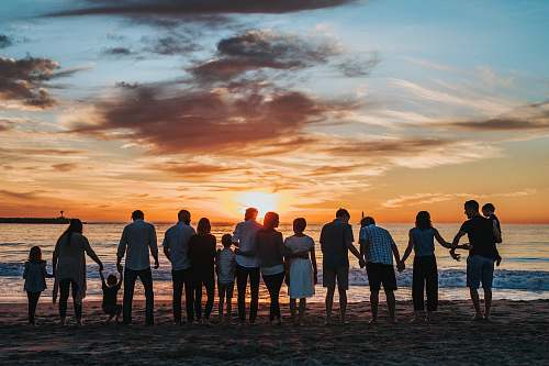 person people standing on shore during golden hour family