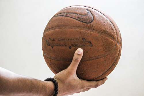 person person holding brown Nike basketball people