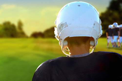 person person wearing NFL helmet during daytime people