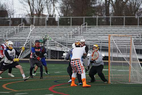 person players playing lacrosse game in field people