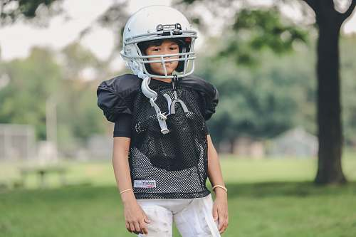 person selective focus photography of boy wearing American football gear people