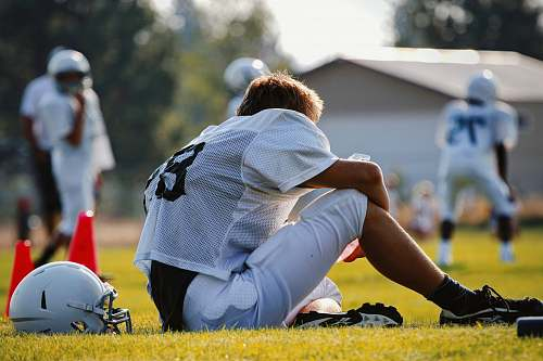 person selective focus photography of man sitting on field wearing football gear people