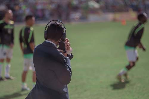 person selective focus photography of man using headphones near athletes people