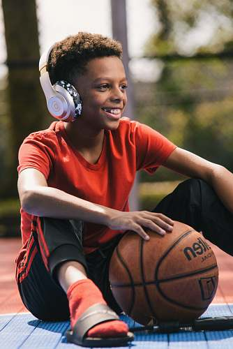 person selective focus photography of smiling boy wearing headphones and holding basketball people