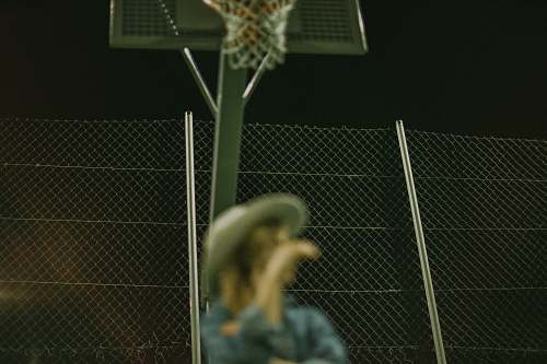 person selective focus photography of woman wearing gray hat on basketball court people