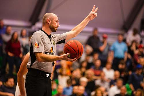 person shallow focus photo of man holding basketball people