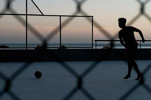 person silhouette of person by ball near sea during golden hour sport