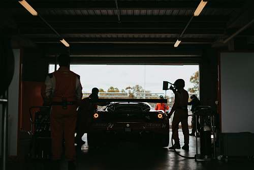 person silhouette photo of men standing front of car inside garage car